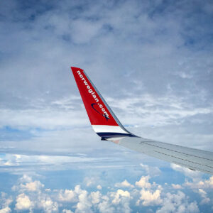 Airplane Wing of Norwegian Airlines in the Clouds